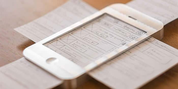 Teléfono con wireframe en papel