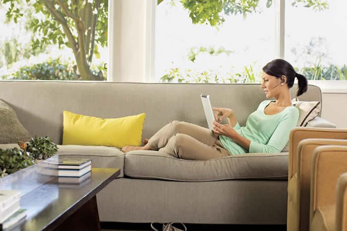 Señorita recostada en un sofá usando su tableta
